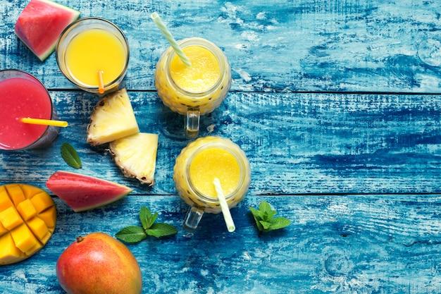 Frullato di mango e ananas fresco in due bicchieri con frutti su uno sfondo rustico in legno torquise