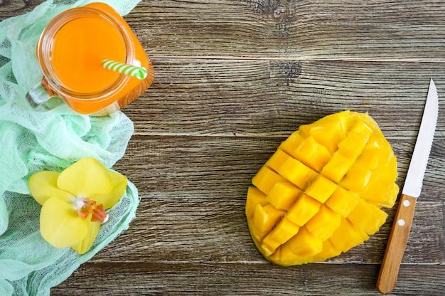 Frullato di mango in un barattolo di vetro e mango fresco su un fondo di legno. frullato di mango. concetto di frutta tropicale. vista dall'alto
