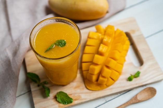 Frullato di mango rinfrescante e sano in un bicchiere con mango