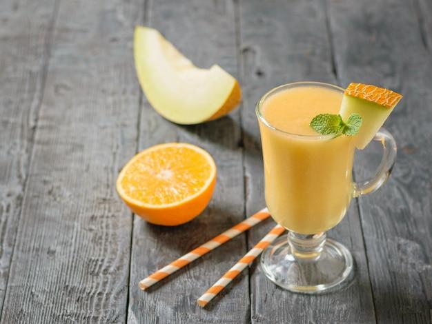 Frullato di melone con tubi da cocktail e arancia su un tavolo di legno.