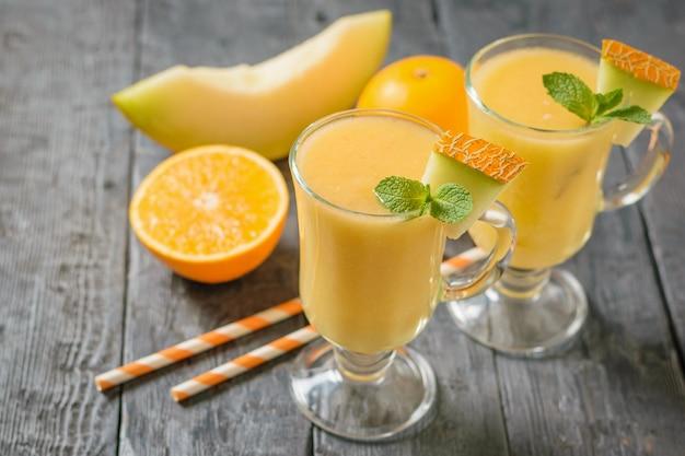 Frullato di melone, melone, menta, arancia e cannucce da cocktail su un tavolo di legno scuro.