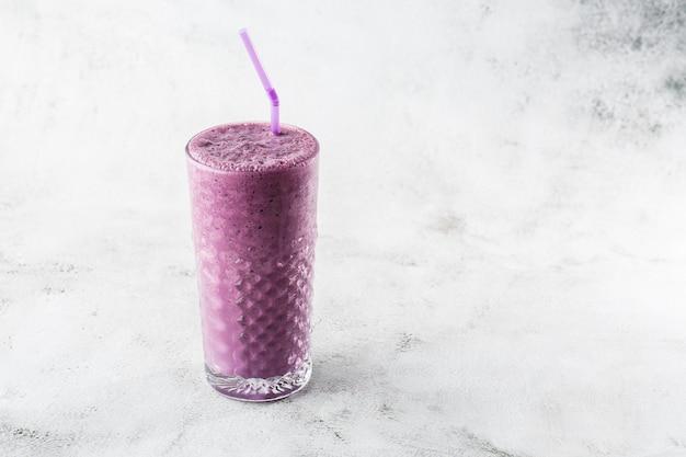 Frullato di mirtilli o frappè viola del ribes nero in vetro su fondo di marmo luminoso. vista dall'alto, copia spazio. pubblicità per menu bar milkshake. menu della caffetteria. foto orizzontale.