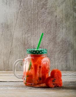 Frullato di succo di anguria in un barattolo di vetro con fetta di anguria e paglia roteato vista laterale su sfondo di legno e grunge