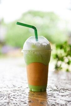 Frullato di tè verde bevande ghiacciate - tè verde matcha con latte su vetro di plastica