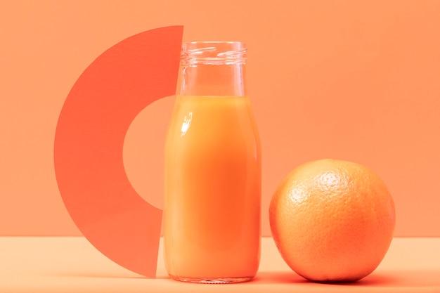 Frullato di vista frontale in bottiglia con l'arancia