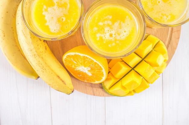 Frullato giallo di mango, banana e arancia su un tavolo di legno bianco.