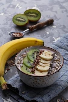 Frullato in una ciotola con semi di banana, kiwi, chia, lino e semi di girasole