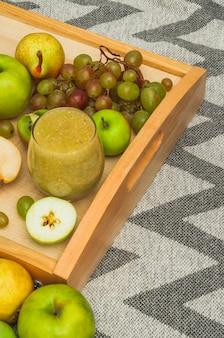 Frullato in vetro e frutta fresca sul vassoio di legno sopra la tovaglia