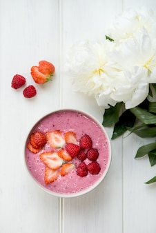 Frullato rosa sano nella ciotola da banana e fragole con pezzi di frutti di bosco in cima