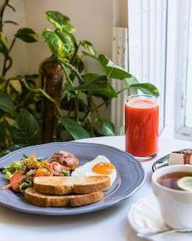 Frullato rosso; colazione e tè sul tavolo bianco vicino alla pianta di epipremnum aureum
