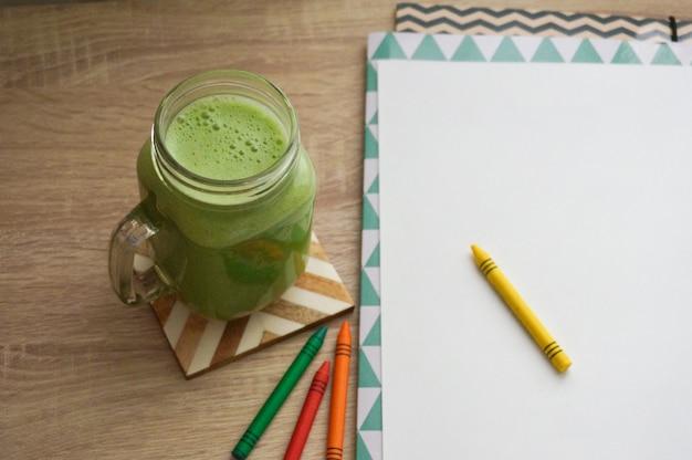 Frullato sano celarey verde sullo scrittorio di legno accanto al foglio di carta bianco