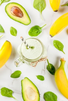 Frullato sano con banana e spinaci baby n sfondo di marmo bianco