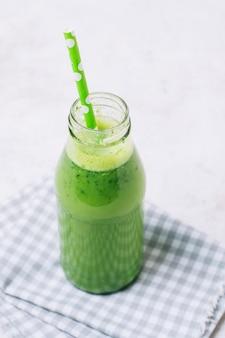 Frullato verde ad alto angolo con paglia verde