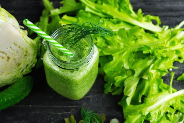 Frullato verde con cetrioli, cavoli e verdi salutari sul tavolo