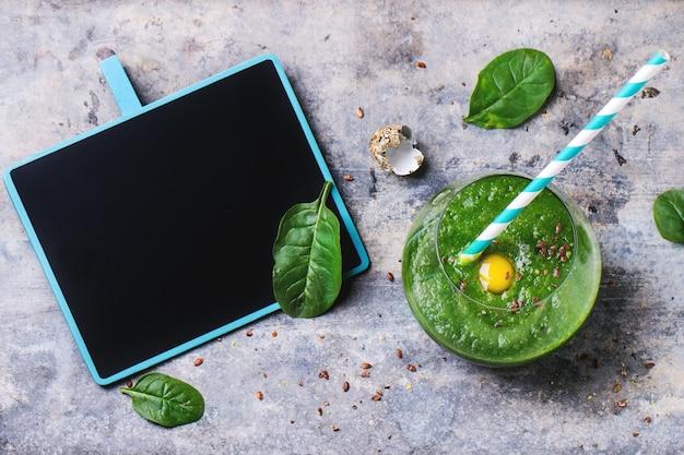 Frullato verde con mela e foglie su calcestruzzo