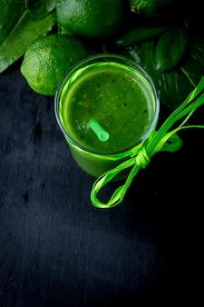 Frullato verde e ingredienti per esso su legno nero. dieta. detox. bevanda salutare vista dall'alto