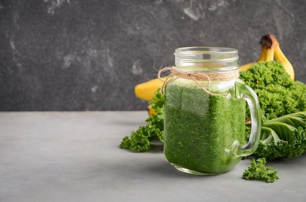 Frullato verde fresco con cavolo e banana in un vaso.