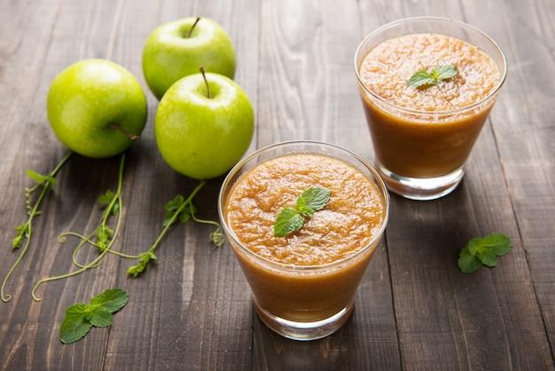 Frullato verde fresco delle mele su fondo di legno