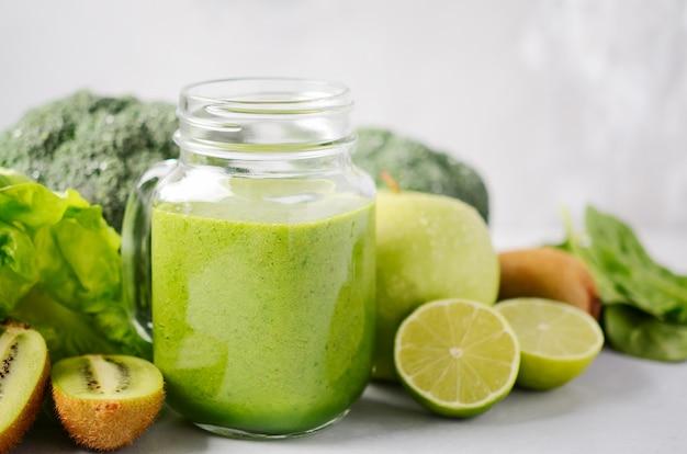 Frullato verde fresco in un barattolo con gli ingredienti su una tavola di cemento grigia.