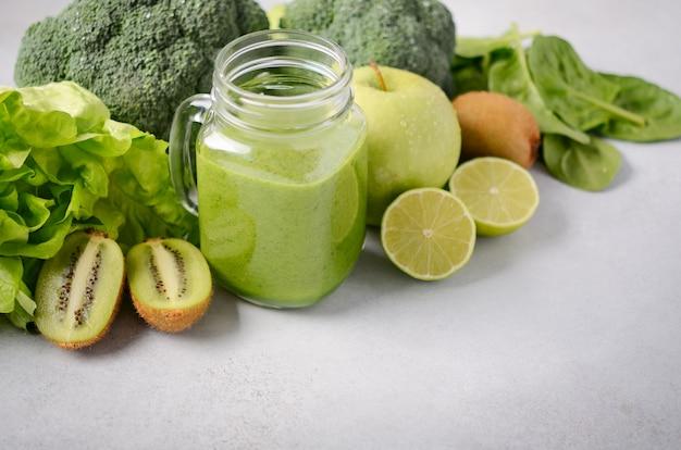 Frullato verde fresco in un barattolo con gli ingredienti