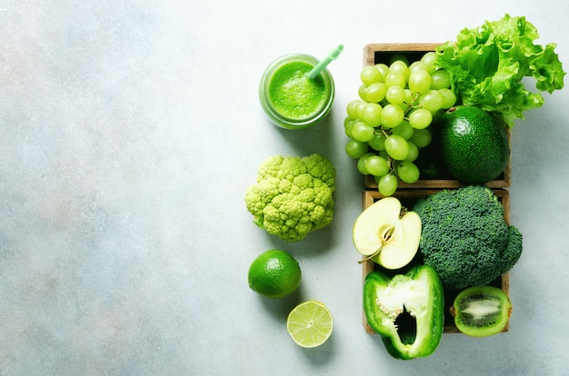 Frullato verde in barattolo di vetro con verdure fresche biologiche e frutta verde su grigio. dieta primaverile, vegetariano crudo sano, concetto di vegano, colazione detox, cibo pulito alcalino. copia spazio