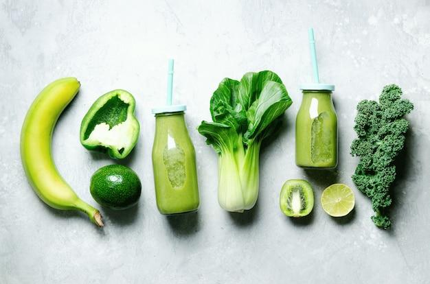 Frullato verde in barattolo di vetro con verdure fresche biologiche e frutta verde su grigio.