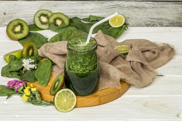 Frullato verde in un barattolo con lime e frutti di bosco