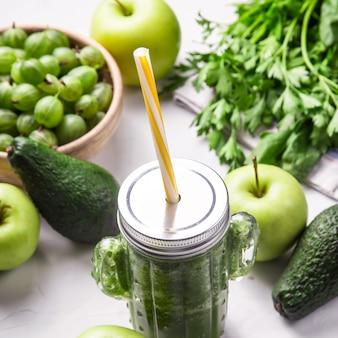 Frullato verde in un bicchiere a forma di cactus tra gli ingredienti verdi