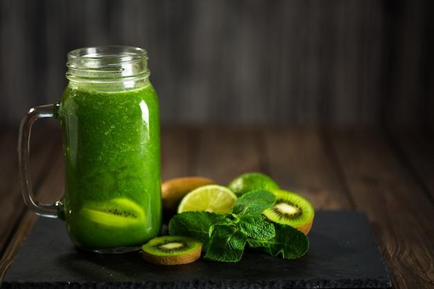 Frullato verde miscelato con ingredienti sul bordo di pietra, legno