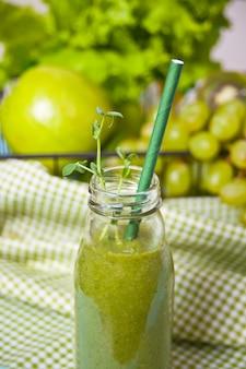 Frullato verde miscelato fresco in bottiglietta di vetro con frutta e verdura. concetto di salute e disintossicazione.