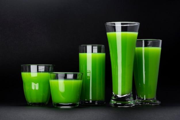Frullato verde organico, succo di mela isolato sul nero con lo spazio della copia, cocktail di sedano fresco