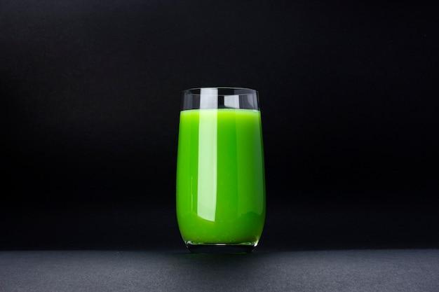 Frullato verde organico, succo di mela su isolato su fondo nero con lo spazio della copia, cocktail fresco