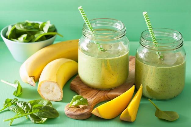 Frullato verde sano con banana di mango di spinaci in barattoli di vetro
