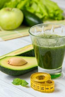 Frullato verde sano con ingredienti su legno bianco