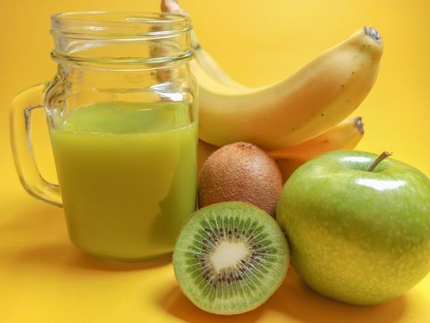 Frullato verde sano in barattolo di vetro: banana, kiwi, mela verde. bevanda sana su sfondo giallo.