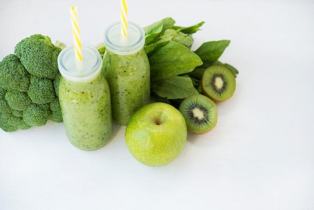Frullato verde vegetariano con verdure e frutta in bottiglie di vetro, copia spazio