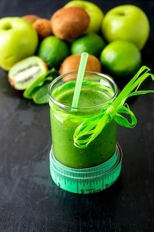 Frullato verde vicino al centimetro ed ingredienti per esso su superficie di legno nera