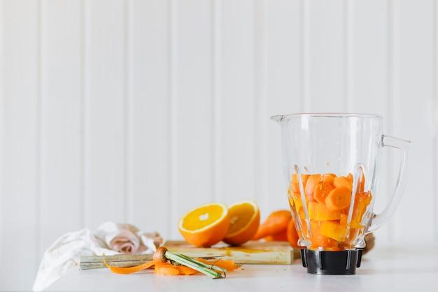 Frullatore con frutta tagliata vicino all'arancia