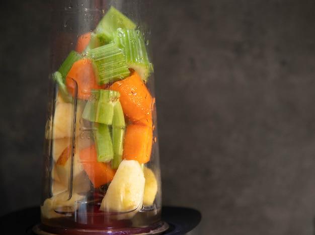 Frullatore con verdure fresche. sedano, mela e carota affettate in una tazza da frullatore per un frullato.
