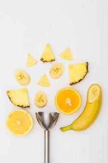 Frullatore elettrico con ananas; fette di banana e arancia isolato su sfondo bianco