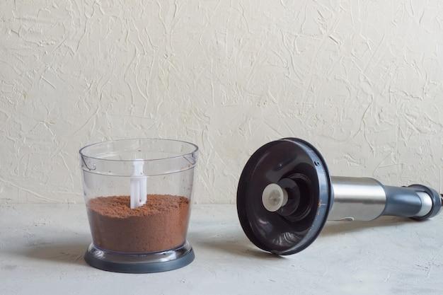 Frullatore sul tavolo della cucina. processo di macinazione delle fave di cacao in un frullatore.