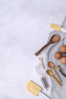 Frusta, cucchiai di legno, spatola in silicone, pennello per imbastire, uova crude, baccello di vaniglia.