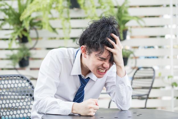 Frustrato giovane uomo d'affari asiatico non è riuscito a sentirsi senza speranza, fallimento del problema aziendale.