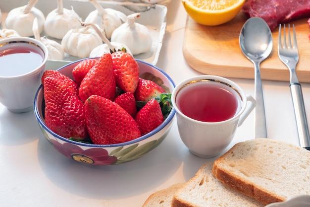 Frutta alla fragola con tè in ceramica stoviglie sul tavolo da pranzo