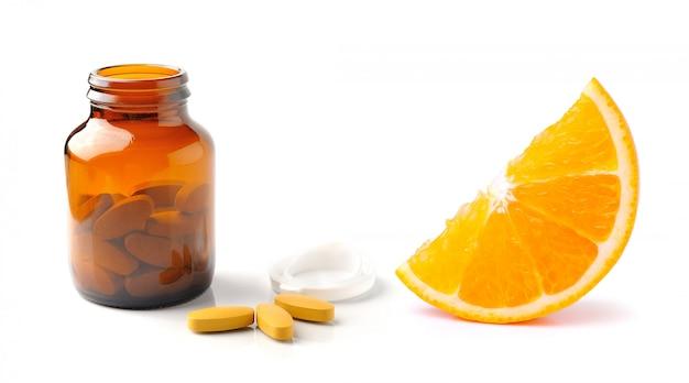 Frutta arancio con la compressa e la bottiglia di vitamina c isolate sul bianco