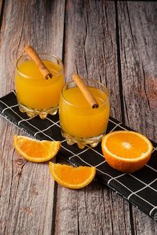 Frutta arancione con un bicchiere di succo di frutta e bastoncini di cannella su un asciugamano nero