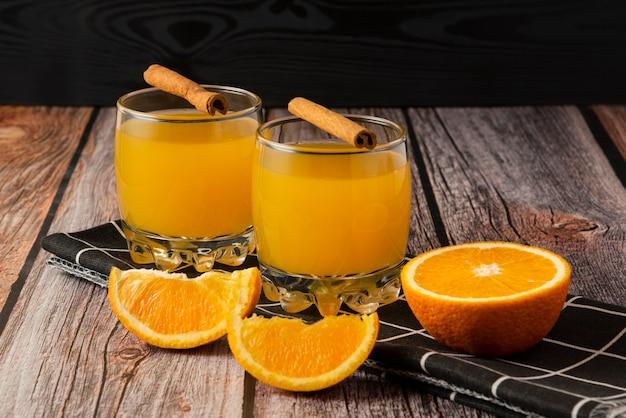 Frutta arancione con un bicchiere di succo e bastoncini di cannella