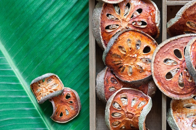 Frutta asciutta di bael in scatola di legno sulla foglia della banana con copyspace