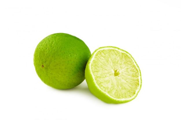Frutta della calce con le fette isolate sulla parete bianca