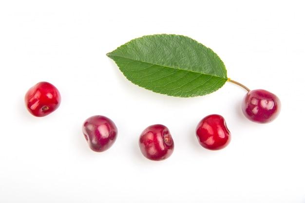 Frutta della ciliegia con la bella foglia con alta vitamina c in composizione in sorriso isolata